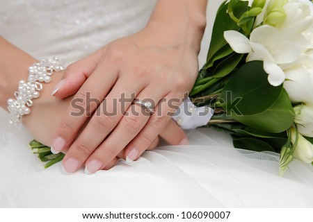 Detail of bridal hand with wedding flowers, focused to the ring - stock photo