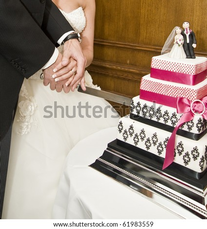 Detail of bride and groom cutting wedding cake after getting married - stock photo