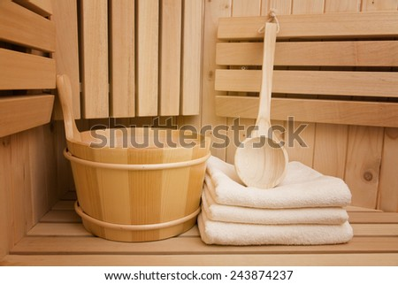 Detail of bucket and white towels in a sauna, wlness and relaxation background - stock photo