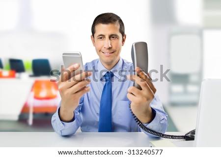 detail of businessman choosing between modern smartphone or landline phone at the office - stock photo
