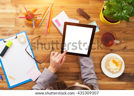 Detail of businessman hands holding blank tablet device. Modern office interior - stock photo