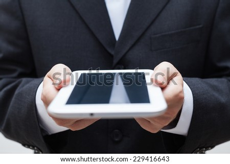 Detail of businessman holding digital tablet. - stock photo
