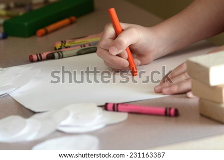 Detail of child coloring on blank white paper with color crayons - stock photo