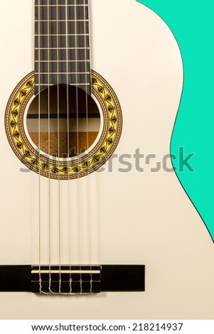 Detail of classic white acoustic wooden guitar with strings and soundboard socket isolated on green background - stock photo