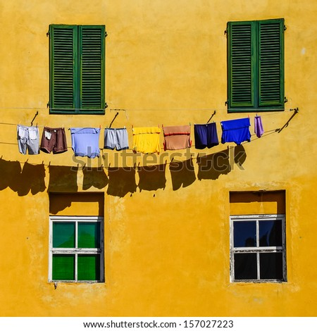 Detail of colorful yellow house walls, windows and drying clothes in square format - stock photo
