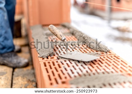 Detail of construction site, trowel or putty knife on top of brick layer - stock photo