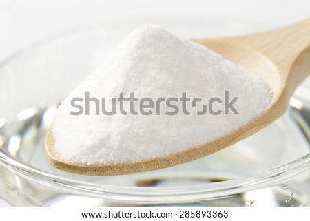 detail of cooking soda on spoon and glass of water - stock photo