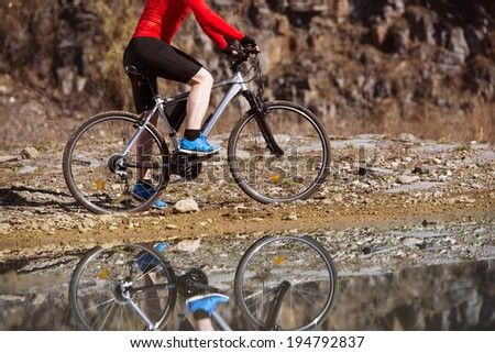 Detail of cyclist man reflecting in water puddle - stock photo