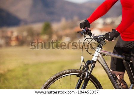 Detail of cyclist man riding mountain bike on outdoor trail in nature - stock photo