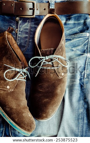 Detail of denim jeans and vintage leather shoes - stock photo