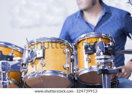 detail of drums while a young male musician is playing set of drums in a recording studio - focus on the top of the left drum - stock photo