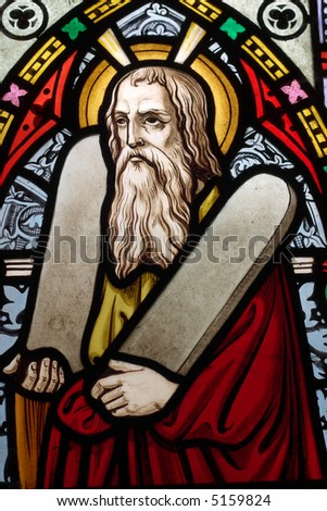 Detail of English, Victorian stained glass church window depicting Moses with the tablets of covenant in his arms, interestingly without text, means he is pictured before climbing Mount Sinai - stock photo