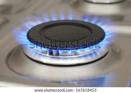 Detail of gas burner with blue flame. - stock photo