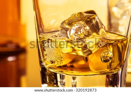 detail of glass of whiskey with ices near bottle on table with reflection, warm atmosphere, time of relax with whisky - stock photo