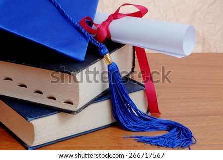 Detail of graduation themed items including blue cap and tassel with diploma tied up with a red ribbon. Both are on top of old books stacked on wooden table top in front of rough textured background - stock photo