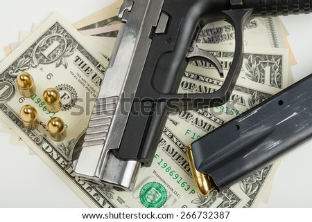 detail of gun with bullet on US dollar banknotes, crime or corruption concept - stock photo