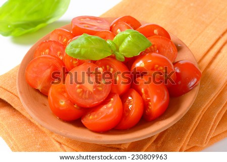 detail of halved cherry tomatoes in the bowl with fabric linen - stock photo