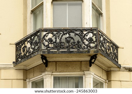 detail of highly decorated balcony railing made in cast-iron  in center of touristic sea town, shot from the public street,  Brighton, East Sussex  - stock photo