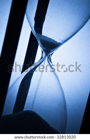 detail of hourglass on blue - stock photo