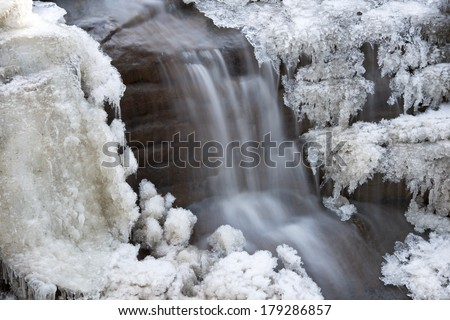 Detail of ice formations surrounding small waterfall in Aurora Canyon at Starved Rock State Park, LaSalle County, Illinois. - stock photo