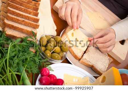 Detail of kitchen table and female hands putting cheese on sandwiches. - stock photo