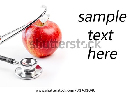 detail of medical stethoscope on red apple on a white background with space for text - stock photo