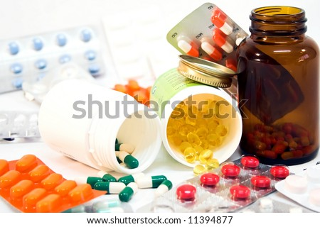 Detail of medicine bottles with spilled pills. - stock photo
