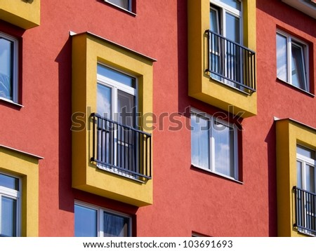 Detail of modern apartments with balconies and red walls - stock photo