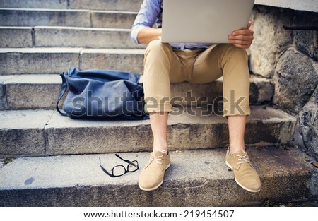 Detail of modern hipster man�´s feet sitting on the stairs and using laptop - stock photo