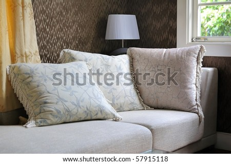 Detail of modern living room with table lamp and pillow cushions on sofa - stock photo