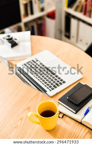 Detail of modern office with yellow cup of tea. - stock photo