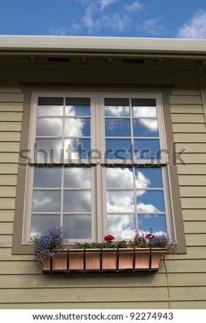 Detail of New Luxury Home: Reflection of Clouds and Blue Sky in Window - stock photo