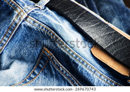Detail of nice blue jeans with leather belt - stock photo