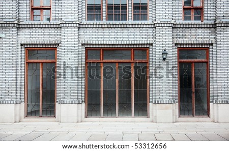 Detail of old Chinese style building facade with arch doors and colorful windows in a town.This is architectural style in the begin of last century's. - stock photo