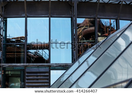 detail of old factories reflection in the windows of a modern building - stock photo