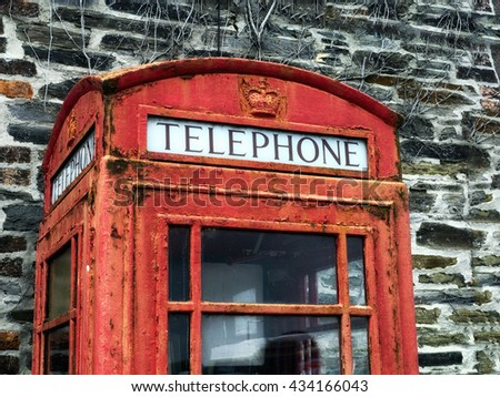Detail of old telephone box; Traditional UK red telephone box; paintwork  faded and peeling due to weathering and age  - stock photo