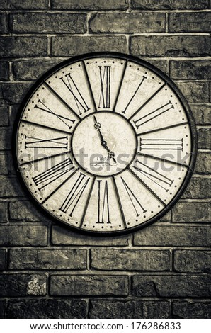 Detail of old vintage clock in monochrome on textured brick wall - stock photo