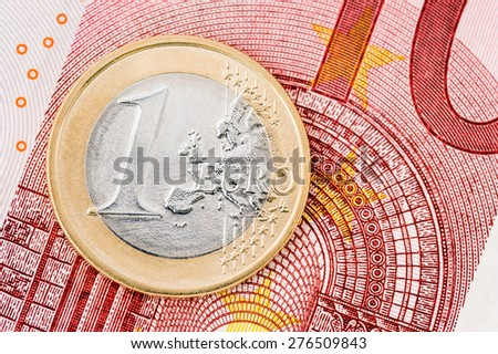 Detail of one Euro coin on red banknote background - stock photo