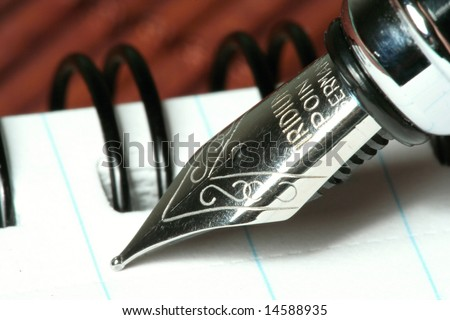 detail of pen with notebook on brown bamboo mat - stock photo