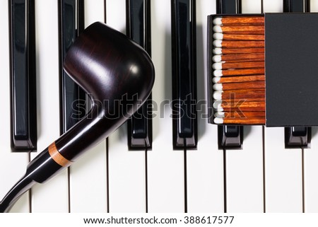 Detail of piano keyboard and  luxury tobacco pipe - stock photo