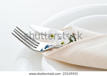detail of place setting with fork knife and little flower - stock photo