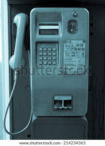 Detail of public phone in a telephone box - cool cyanotype - stock photo