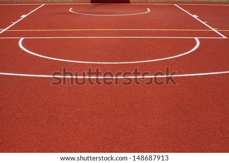 detail of red public outdoor basketball court - stock photo