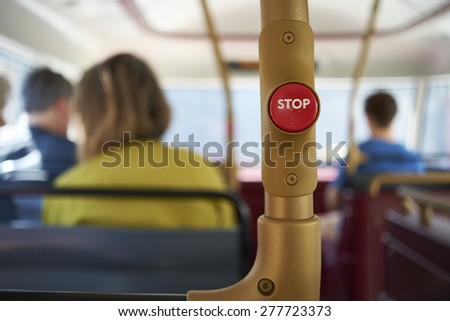 Detail of red stop button inside double decker bus in London, UK, with passengers seated in the blurred background. - stock photo