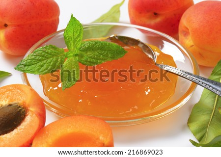 detail of ripe apricots and bowl of apricot jam - stock photo