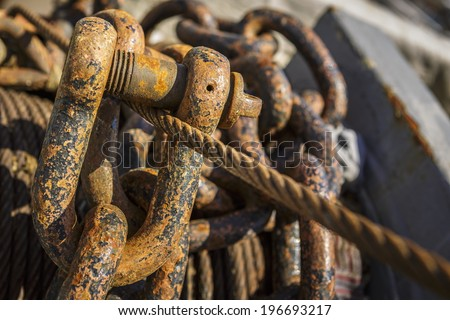 Detail of rusted anchor chains and rigs on the deck of an old sailing ship. Selective focus. - stock photo