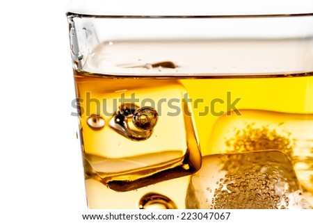 detail of scotch whiskey in glass with ice cubes isolated on white background - stock photo