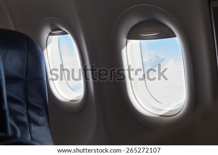 Detail of seat and windows inside an aircraft. - stock photo