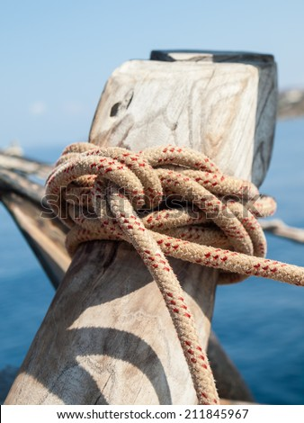 detail of ships rope tied off on a wooden bollard with sea behind - stock photo