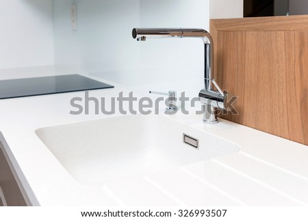 Detail of sink with tap on white worktop of contemporary kitchen - stock photo